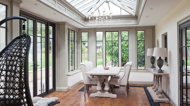 Traditional Conservatory Featuring Bronze Double Doors And Windows.