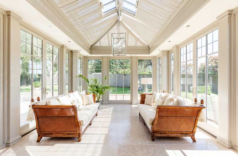 Interior of light filled orangery with roof blinds.