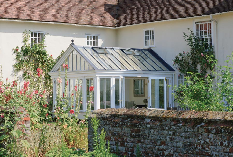 Pretty cottage garden glasshouse in an ideal setting