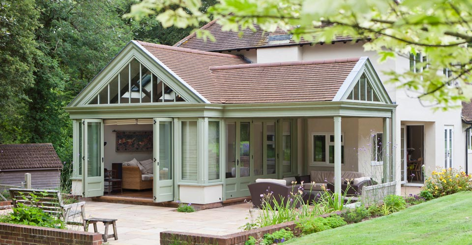 A beautiful tiled roof conservatory with folding doors creating the perfect garden room