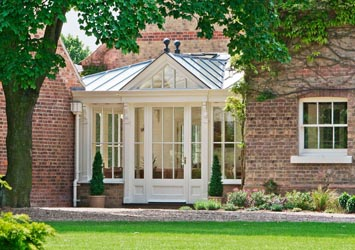 A linking conservatory with decorative pilasters and traditional glazing.