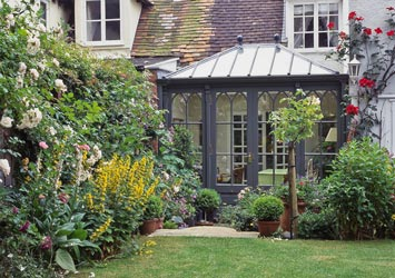A home-office conservatory with gothic arched window design.