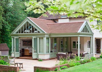 Conservatory with terracotta tiled roof and extending veranda area.