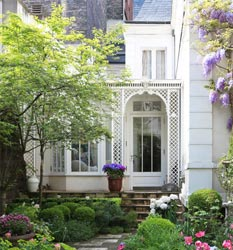 Parisian townhouse conservatory with decorative metal lattice columns.