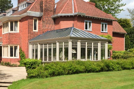 Pretty conservatory with folding doors provides a light filled sitting room for a home in Yorkshire
