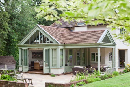 This conservatory in Hampshire opens on to the garden with folding doors and a veranda seating area
