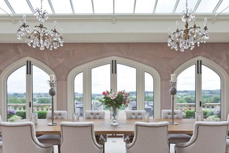 A striking solid construction orangery with arched timber, double doors with bronze inserts.